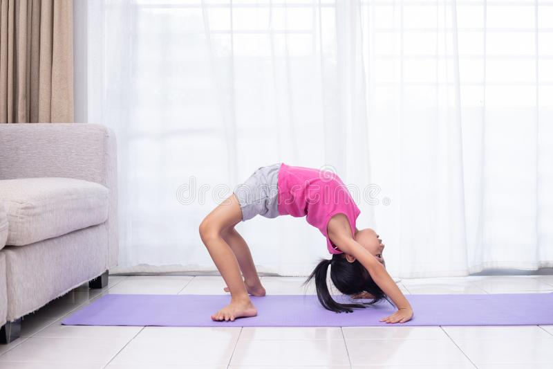 Pose praticando da ioga da menina chinesa asiática em uma esteira foto de stock