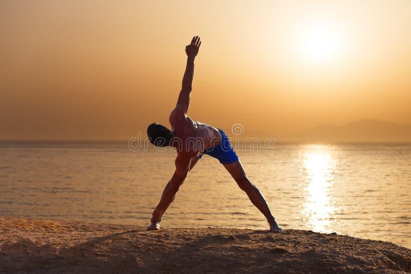 Pose praticando do asana da ioga do homem atlético novo perto da praia do mar imagens de stock