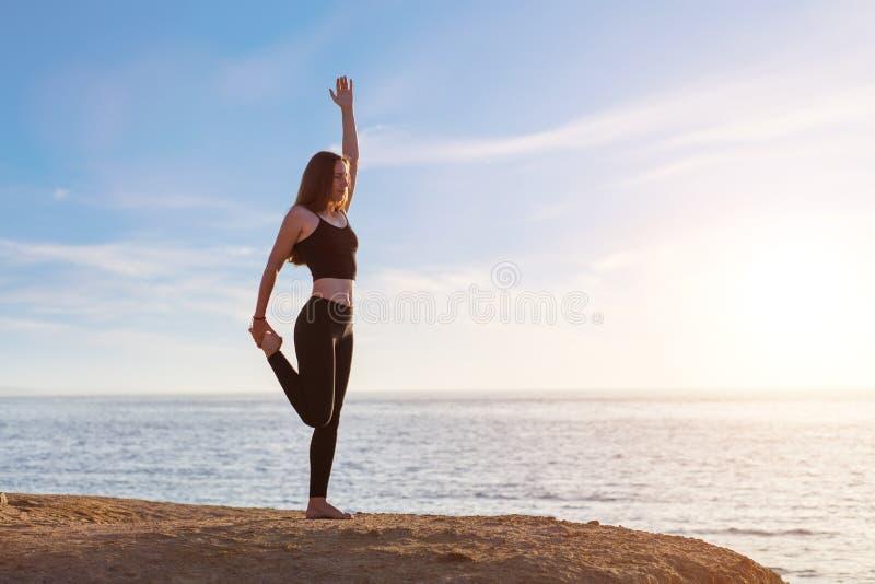 Pose praticando do asana da ioga da jovem mulher na manhã no mar fotos de stock royalty free