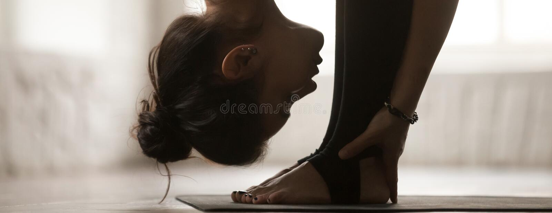 Pose praticando do uttanasana da mulher horizontal da imagem que faz o exercício dianteiro da curvatura imagens de stock