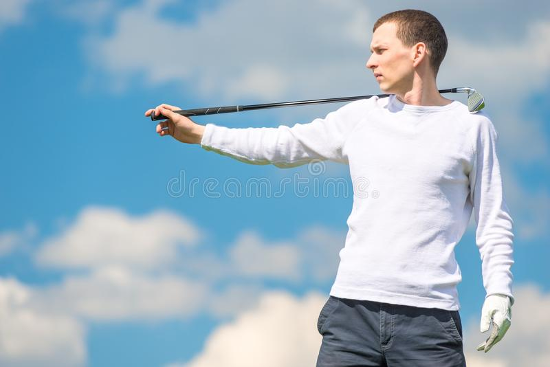 Pose professionnelle de golfeur sérieux avec le club de golf sur le Ba de ciel bleu image libre de droits