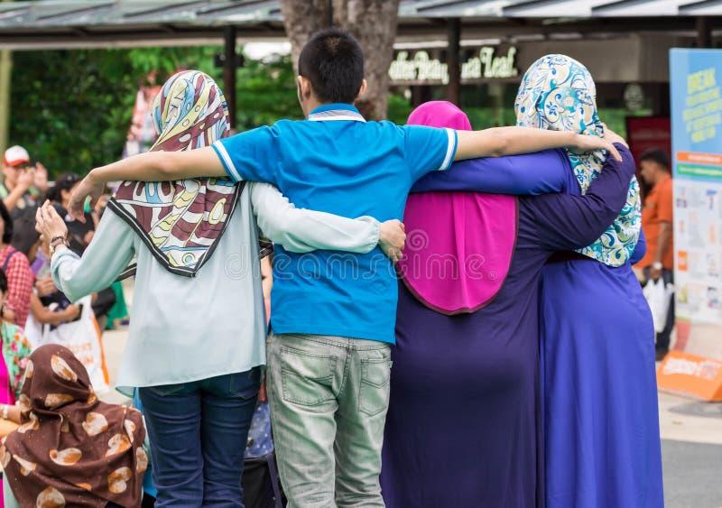 Pose racial da harmonia de diversas mulheres muçulmanas no parque de Sentosa Merlion, Singapura, o 15 de março de 2019 fotografia de stock