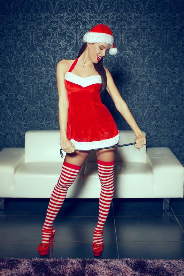 Pose sexy de femme de Santa d'intérieur avec le fouet à Noël images libres de droits