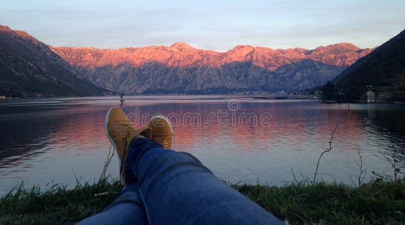 Pose sur l'herbe entre les montagnes rocheuses et la mer image stock