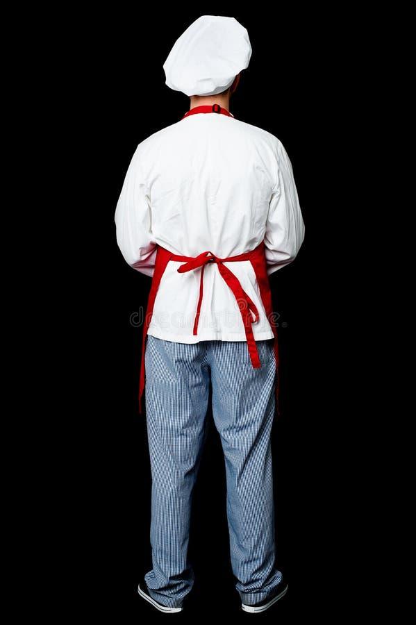 Pose traseira de um cozinheiro chefe masculino no uniforme foto de stock