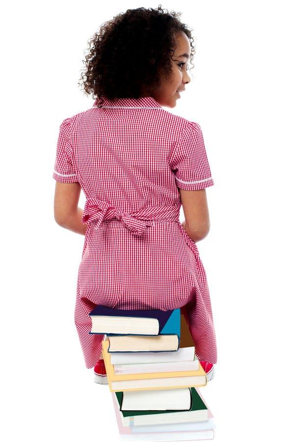 Pose traseira de uma menina que senta-se em uma pilha dos livros imagem de stock