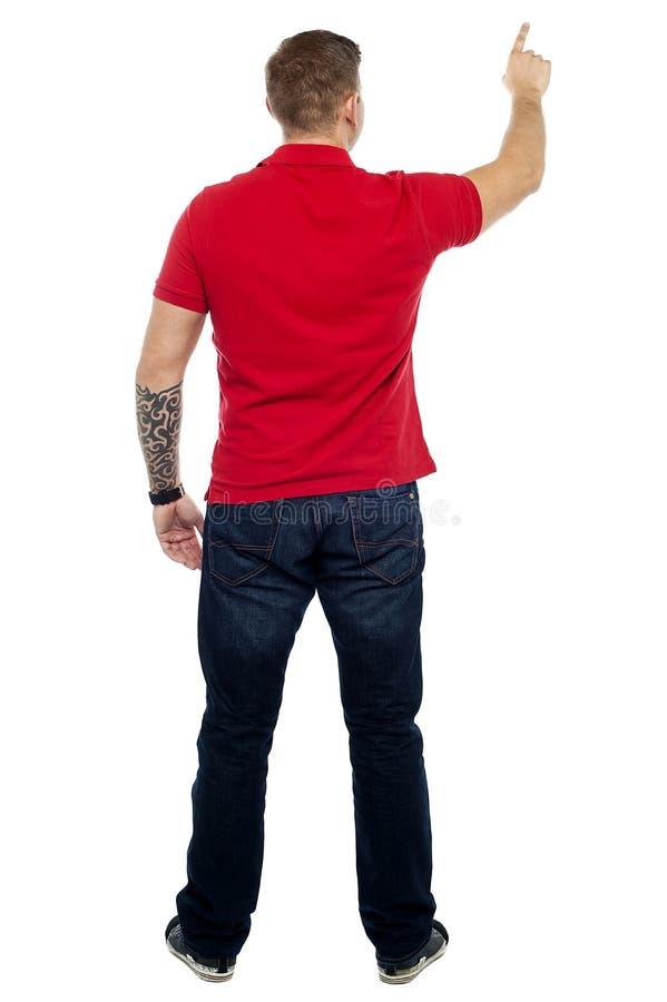 Pose traseiro do homem que aponta na área de espaço da cópia fotos de stock royalty free