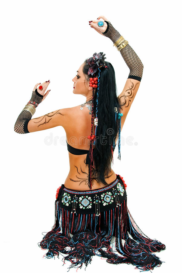 Pose in tribal dance. Alluring lines of sitting tribal dancer on white stock image