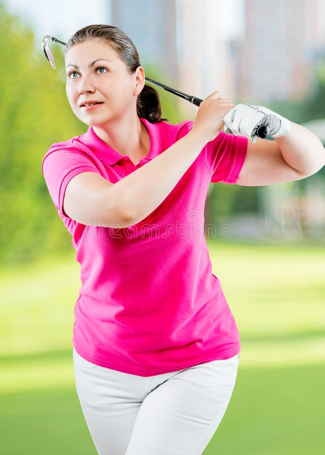 Pose woman golfer after hitting a ball club stock photography