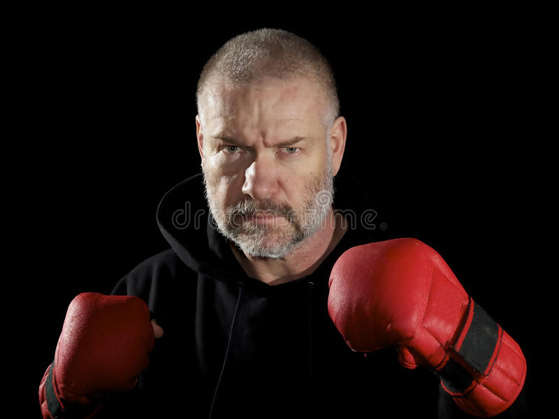 Posed fighter wearing gloves. Isolated on black stock images