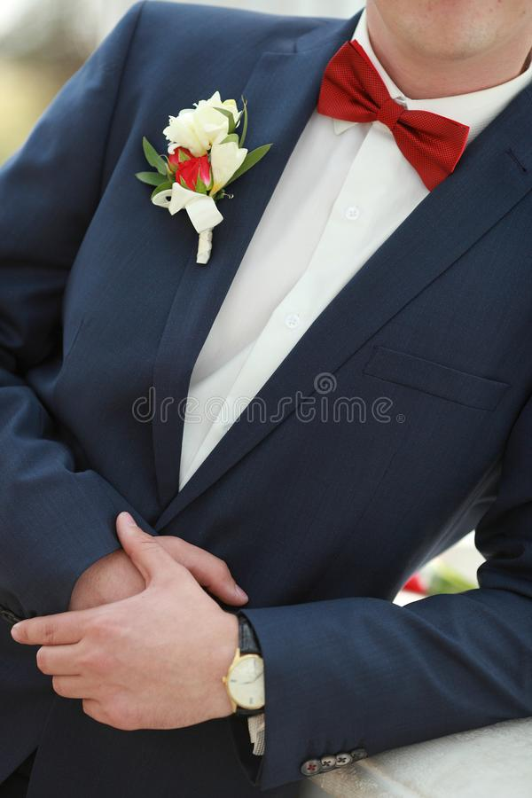 Posed groom with button hole.Wedding details, beautiful boutonniere, men`s details. Posed groom with button hole.Wedding details, beautiful boutonniere royalty free stock images