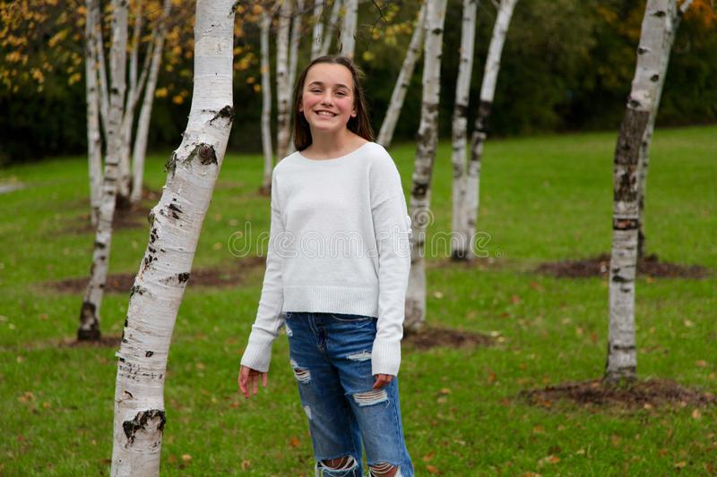 Young girl smiling in a forest of birch trees. Posed model outdoor portrait shot in Canada royalty free stock photography
