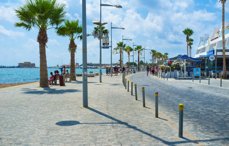 The Poseidon Ave. PAPHOS, CYPRUS - AUGUST 3, 2014: The busy promenade with many street cafes and bars and the medieval castle on the background, on August 3 in stock image