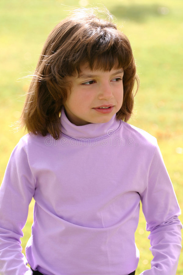 Poser. Adorable young Hispanic American girl with pink/purple turtle neck posing like a model. If you like this photo, please see my portfolio for more from this stock image