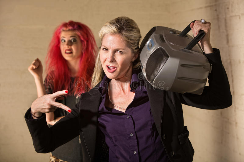 Poser Mother with Teen. Silly mature European women playing radio near startled teenager stock images