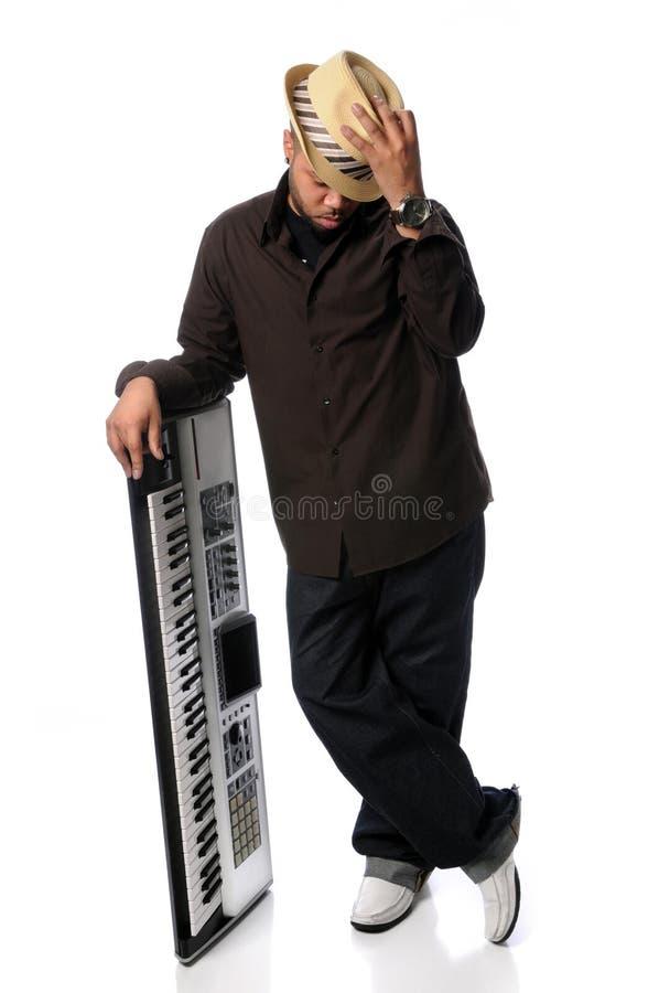 posera barn för tillsammans med elektriskt manpiano arkivbild