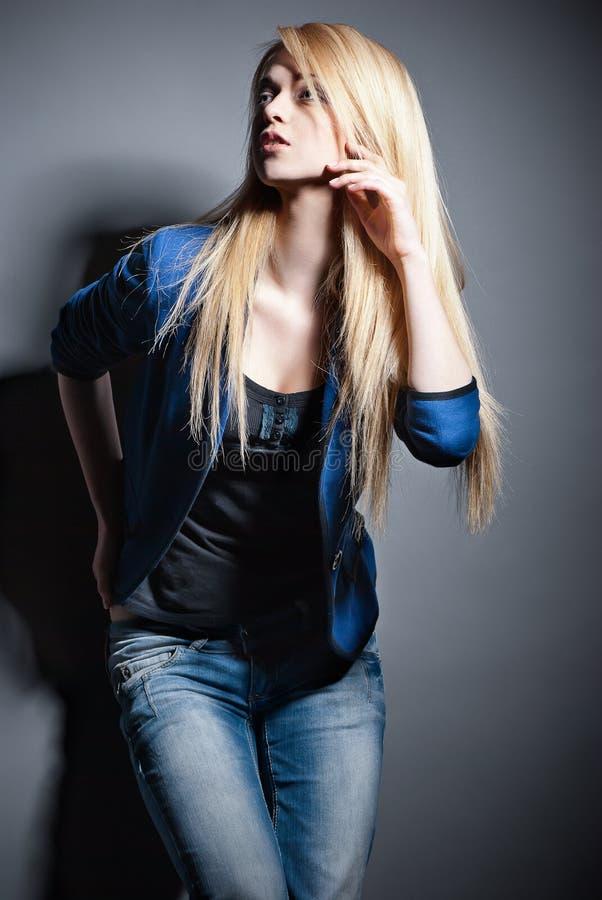 Posera den blonda kvinnan med långt hår på grå färger royaltyfri fotografi