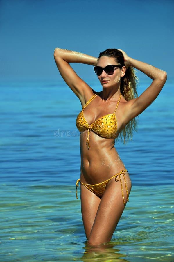 Posera för bikinimodell som är sexigt framme av kamera på den tropiska stranden royaltyfri bild