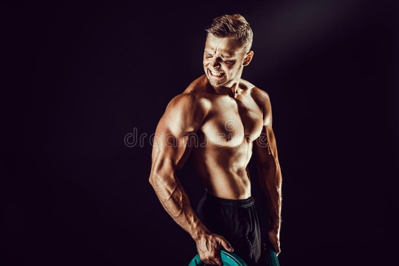 posera för kroppsbyggare Kondition tränga sig in man på mörk bakgrund royaltyfria foton