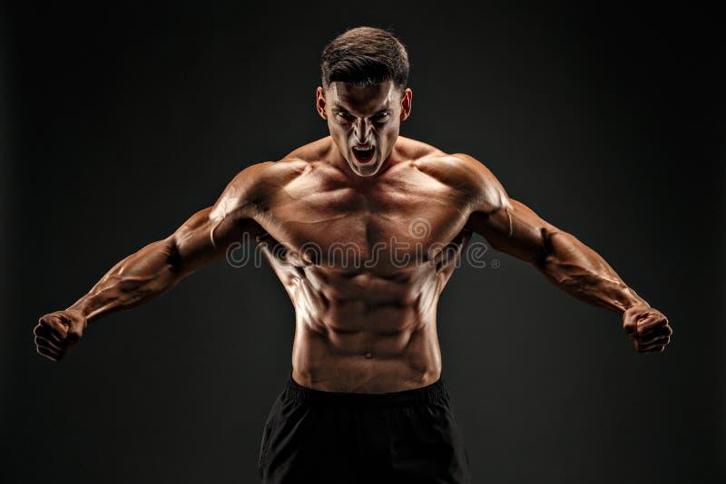 posera för kroppsbyggare Kondition tränga sig in man på mörk bakgrund Vråla för motivation royaltyfri foto