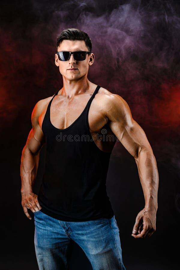 posera för kroppsbyggare Manlig makt för härlig sportig grabb Kondition tränga sig in man i skjorta royaltyfri bild
