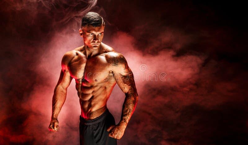 posera för kroppsbyggare Tatuerad kondition tränga sig in mannen på röd rökbakgrund royaltyfri foto