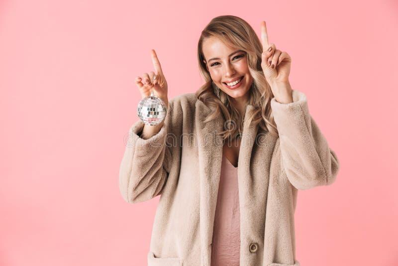 Posera för kvinna som isoleras över laget för mode för rosa väggbakgrund som det iklädda rymmer den lilla diskobollen arkivbilder