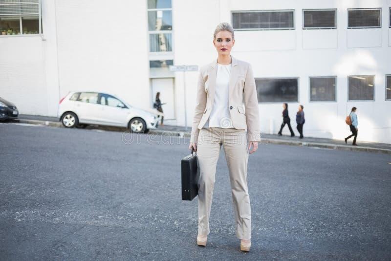 Posera för portfölj för allvarlig stilfull affärskvinna hållande arkivbild