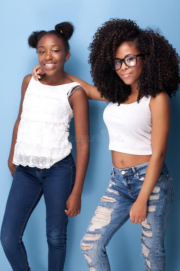 Posera för två härligt ungt systrar fotografering för bildbyråer