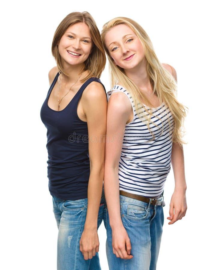 Posera för två ungt lyckligt kvinnor royaltyfri bild