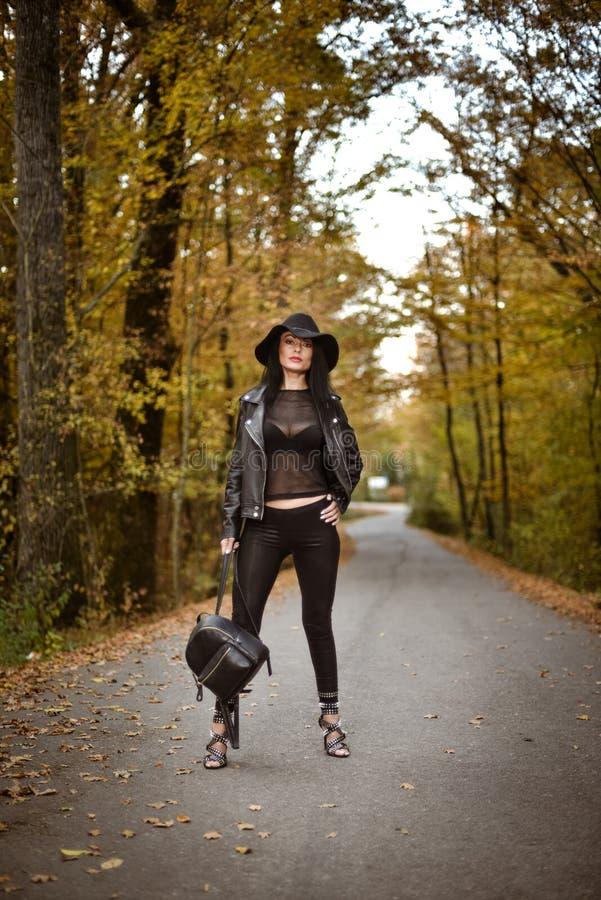 Posera för ung kvinna en höstdag på en väg i träna royaltyfri bild