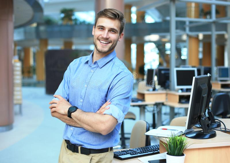 Posera för ung man som är säkert och som är positivt i yrkesmässigt arbetsplatskontor med utrymme arkivbilder