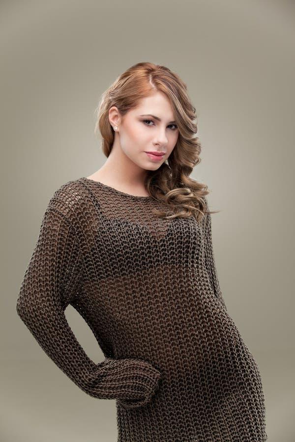 posera kvinna för blond lockig knitwear royaltyfri bild