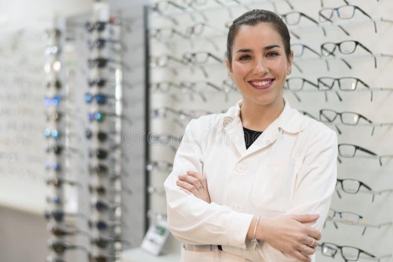 Posera optometrikerkvinnan i glasögon lagra att le att se royaltyfria foton