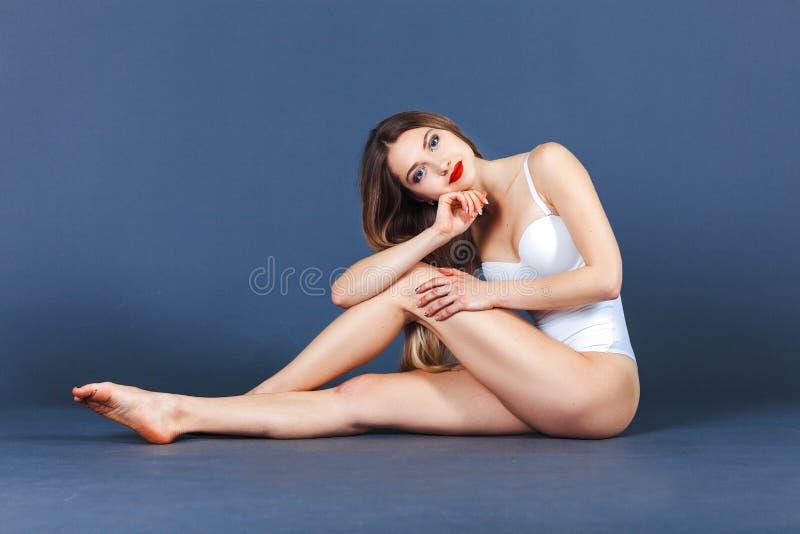 posera studio för modemodell Färdig kvinna i baddräkt Härlig och sund kvinna som poserar över blå bakgrund royaltyfri fotografi