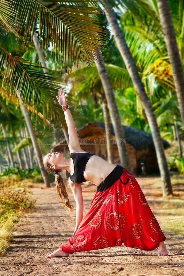 posera triangeltrikonasanayoga royaltyfria bilder