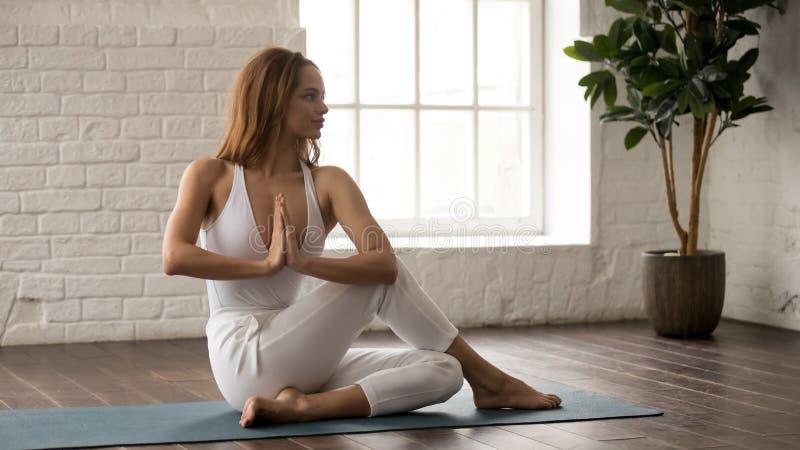 Poserar övande yoga för den attraktiva kvinnan som sitter i Ardha Matsyendrasana arkivfoton