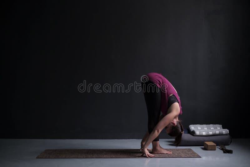 Poserar övande yoga för den sportiga kvinnan, den stående framåt krökningövningen, uttanasana royaltyfri fotografi