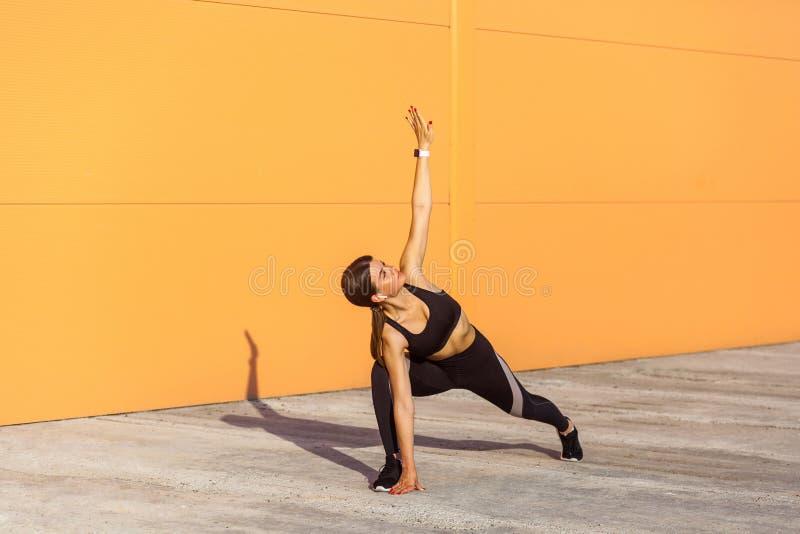 Poserar övande yoga för den unga härliga yogikvinnan som gör utthitatrikonasanaövning, den fördjupade triangeln, att utarbeta som royaltyfri fotografi