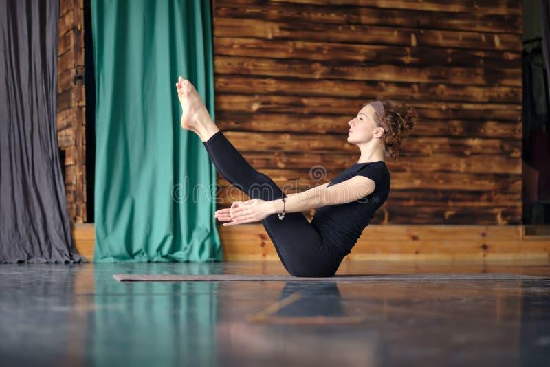 Poserar övande yoga för kvinnan som sitter i jämviktsövning, Paripurna Navasana arkivbild