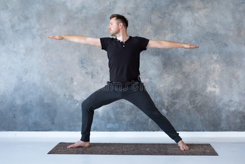 Poserar övande yoga för man i studion som gör krigare 2 royaltyfri foto