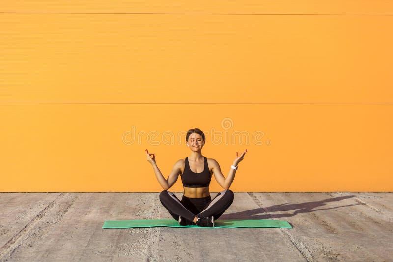 Poserar övande yoga för ung sportig attraktiv kvinna och att göra ardhapadmasanaövningen som mediterar i halv lotusblomma, med mu royaltyfria bilder