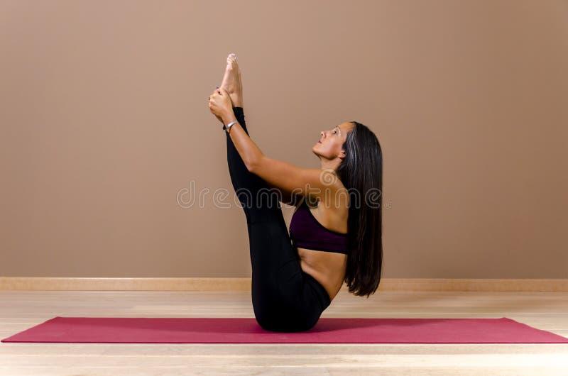 Poserar attraktivt ungt för sidosikt i yoga royaltyfria foton