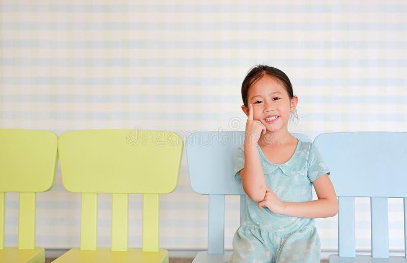 Poserar den förskole- flickan för det lyckliga asiatiska barnet i ett dagisrum på plast- behandla som ett barn stol fotografering för bildbyråer