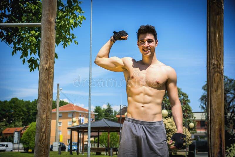 Poserar den idrotts- unga mannen för den Shirtless passformen som gör bicepen royaltyfria bilder