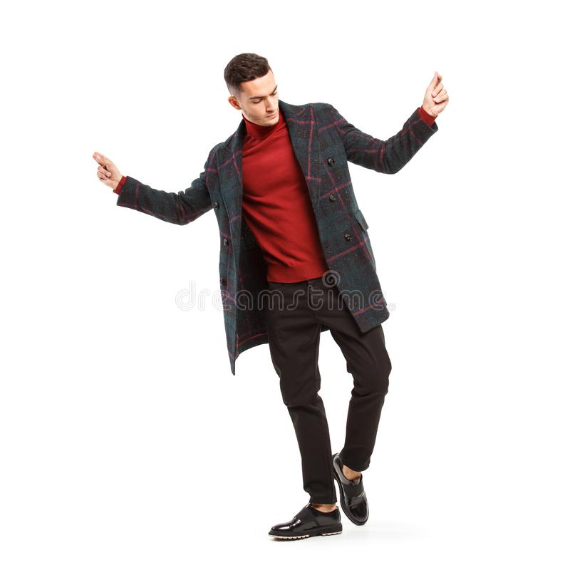 Poserar den iklädda röda halvpolokragen för den unga stilfulla mannen, bruna flåsanden och ett plädlag på den vita bakgrunden arkivfoton