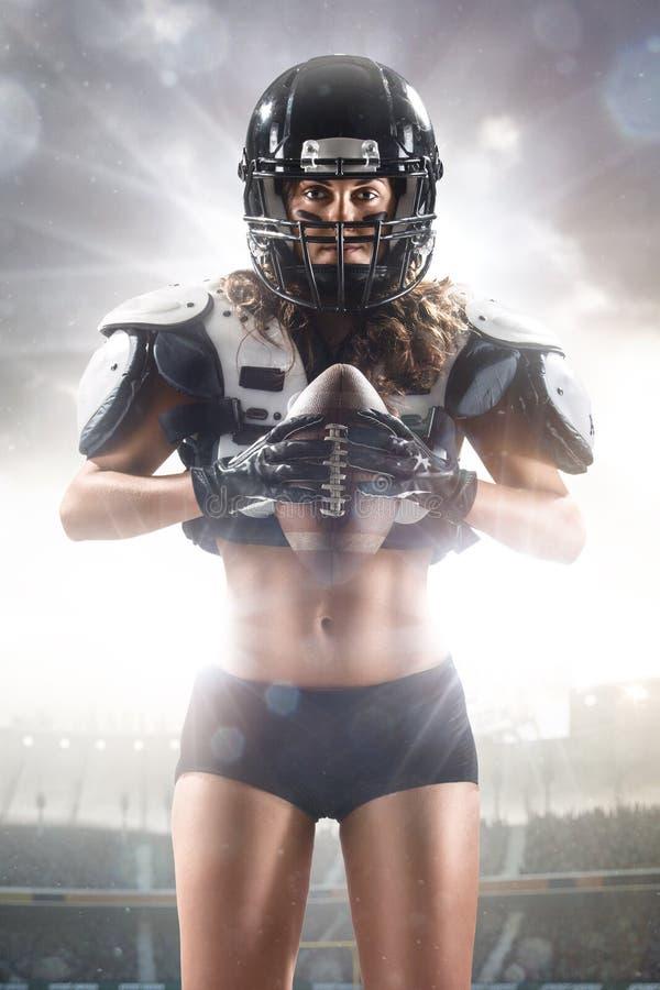 Poserar den kvinnliga spelaren för amerikansk fotboll royaltyfri bild