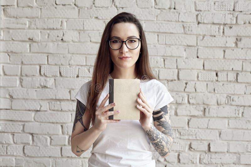 Poserar den nätta hipsteren tatuerade kvinnan i den vita t-skjortan som isoleras på den vita tegelstenväggen, hållen en bok i han royaltyfria bilder