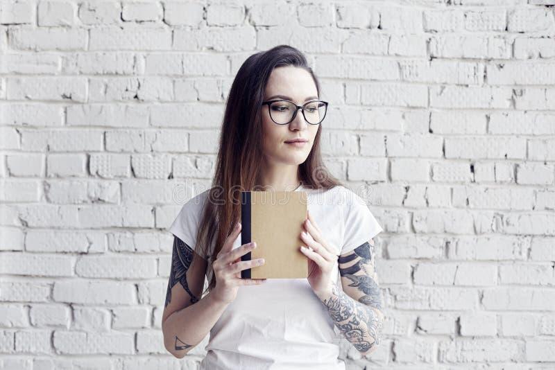Poserar den nätta hipsteren tatuerade kvinnan i den vita t-skjortan med bok I arkivfoto