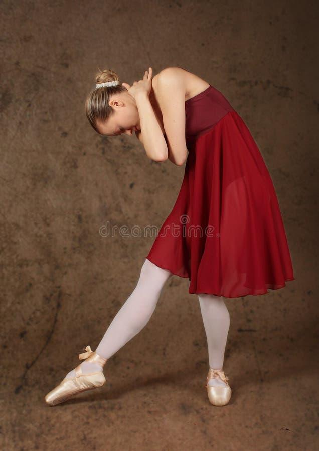 Poserar den röda klänningdansen för ballerina brun bakgrund arkivfoton